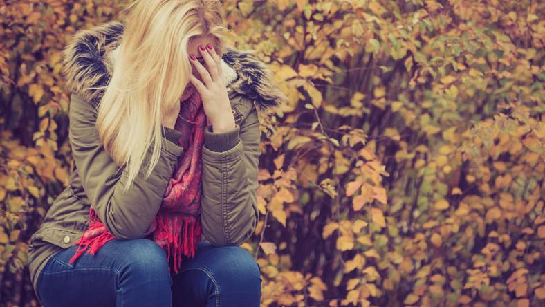 Jesienny spacer: smutna kobieta