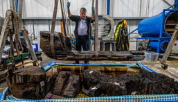 Researcher lifts up coffin containing the remains of a man and a perfectly preserved axe.