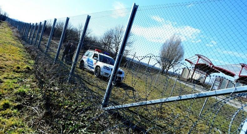 Local police officials patrol in front of a part of the border fence of the Hungarian-Croatian border at the Beremend border crossing point on February 23, 2017