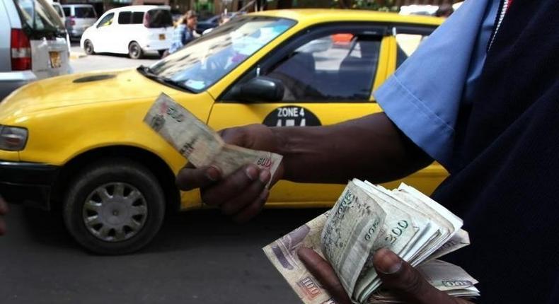 A fuel attendant handles Kenyan shilling notes at a petrol station in the capital Nairobi   REUTERS/Noor Khamis