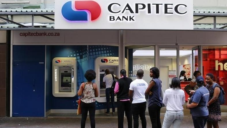 Customers queue to draw money from an ATM outside a branch of South Africa's Capitec Bank in Cape Town in this picture taken March 15, 2016.