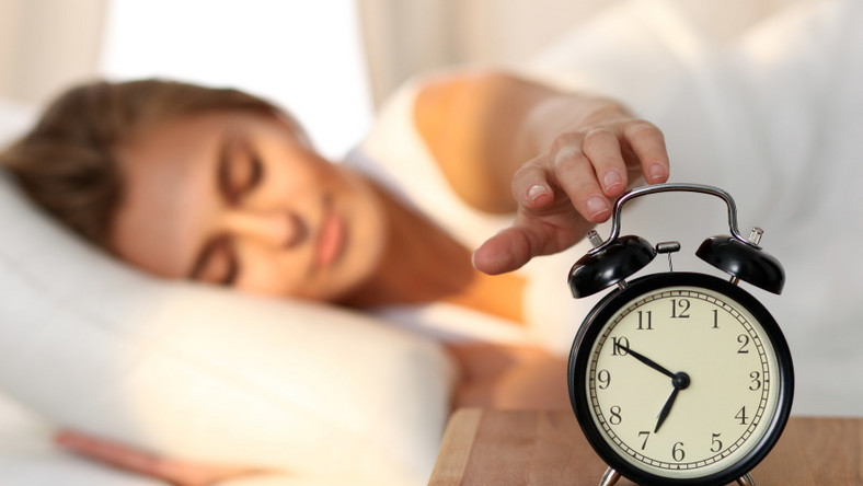 Kobieta w łóżku wyłącza budzik