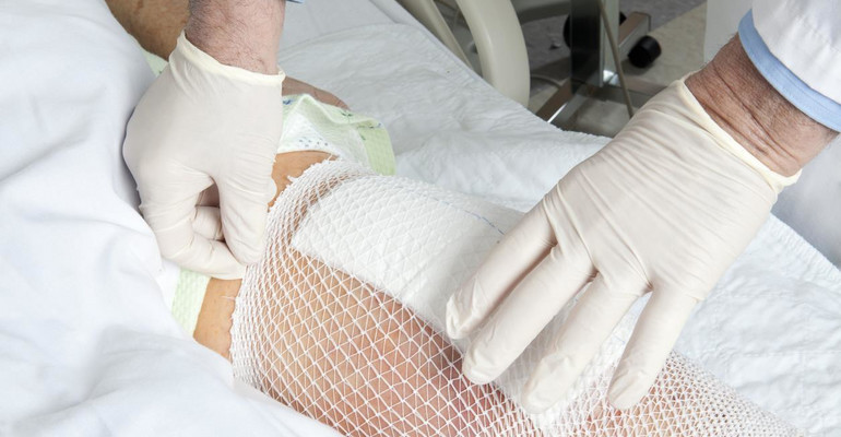 Mesh holds a knee replacement bandage in place.