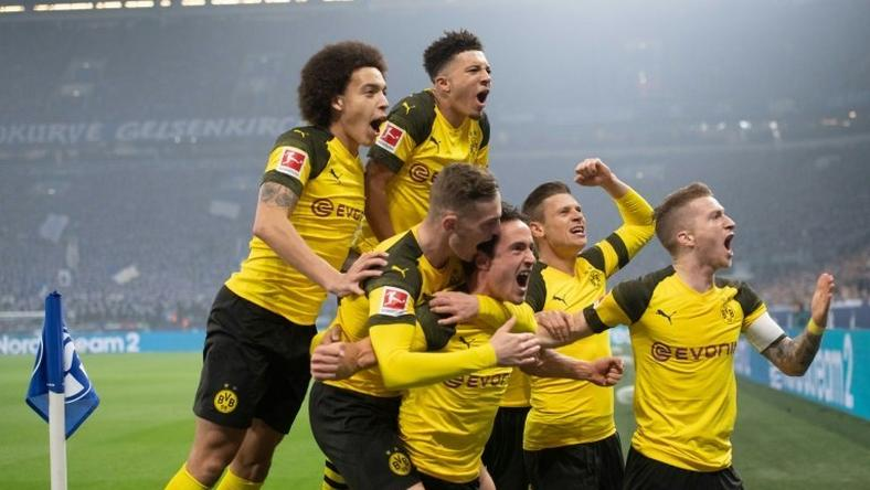 Thomas Delaney (bottom centre) is mobbed by his Dortmund team-mates after scoring against Schalke