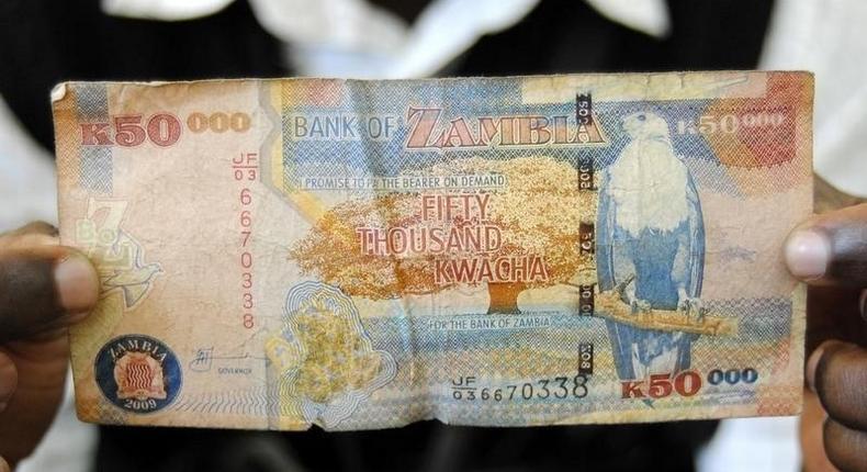 A man displays a 50,000 Kwacha note in Lusaka January 23, 2012. REUTERS/Mackson Wasamunu