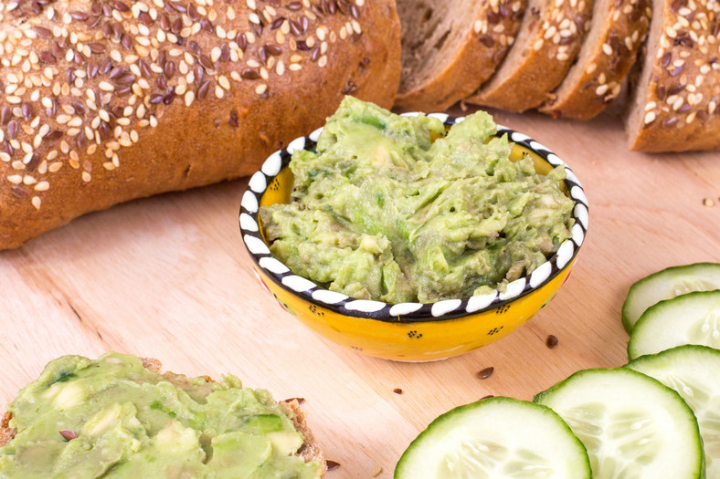 Cucumber and avocado sandwiches on bread background.