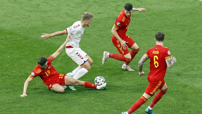 Walijczyk David Brooks (L) faulujący Duńczyka Andreasa Corneliusa (2L) podczas meczu w Amsterdamie