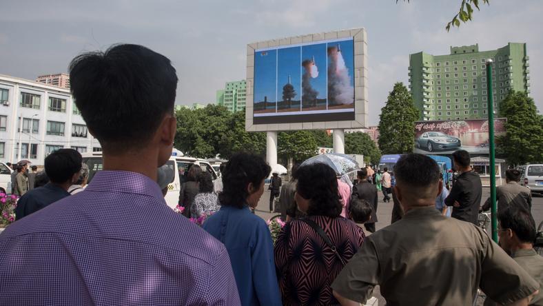 Ludzie na ulicy w Pjongjangu oglądają próbę rakietową