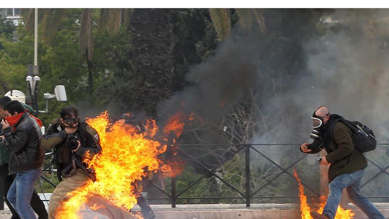 Fotoreporter w płomieniach podczas starć manifestantów z policją. Protest przeciwko cięciom budżetowym. Ateny, Grecja, 23 lutego 2011