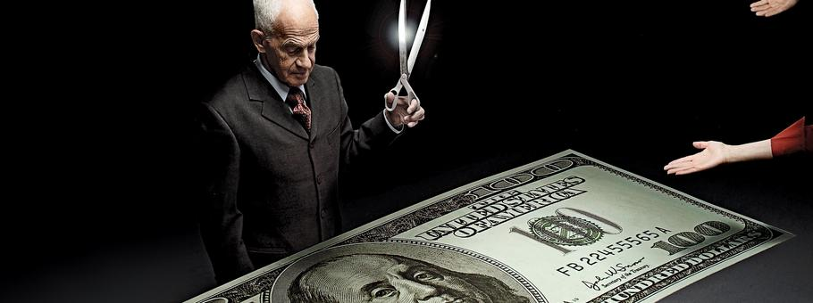 Businessman holding scissors and reaching hands around one hundred dollar bill