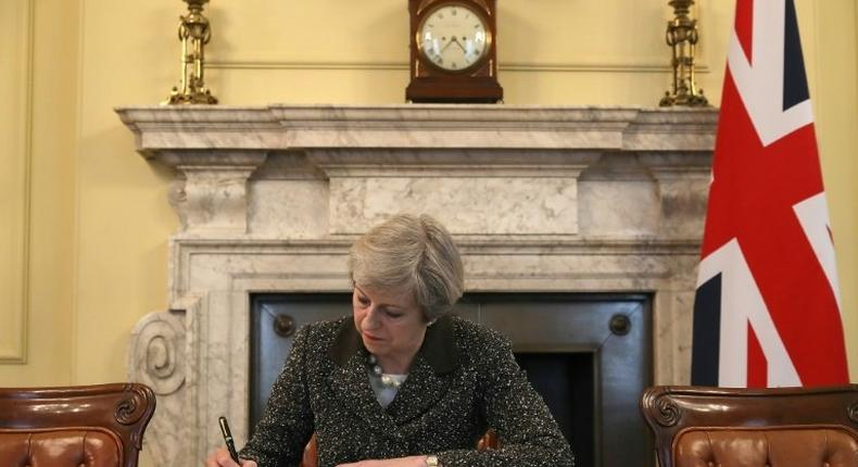 Britain's Prime Minister Theresa May signs a letter to European Council President Donald Tusk invoking Article 50 and signalling the UK's intention to leave the EU, in the cabinet office inside 10 Downing Street on March 28, 2017