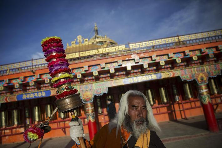 Padma Tsering, a popular Tibetan Buddhist monk spins his prayer wheels at a monastery above the Laru