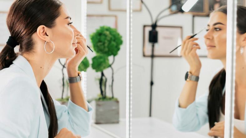 Kobieta przed lustrem. Makijaż.