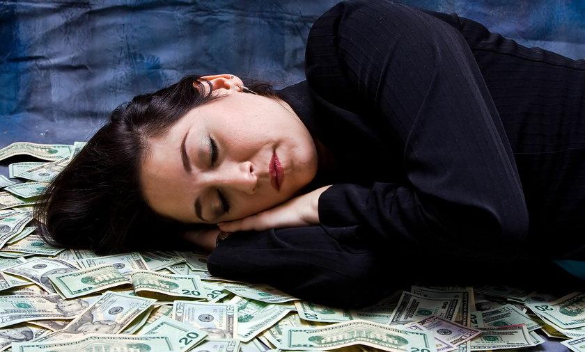 Kobieta śpiąca na pieniądzach