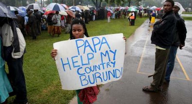 A woman holds a banner written Papa Help My Country Burundi before a mass by Pope Francis, as rain falls in Kenyas capital Nairobi, November 26, 2015.