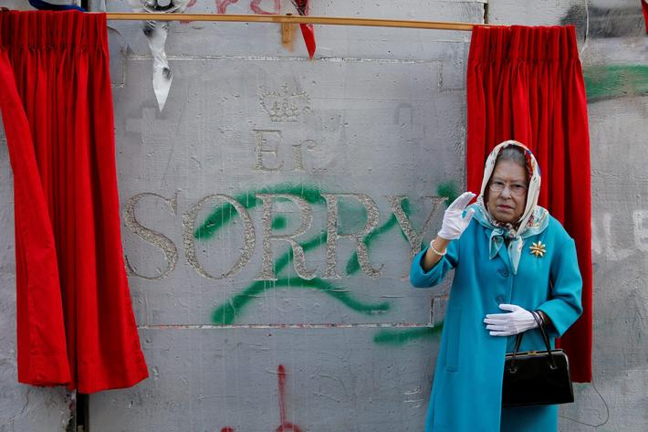 A person, dressed as Britains Queen Elizabeth II, gestures during an event ahead of the anniversary