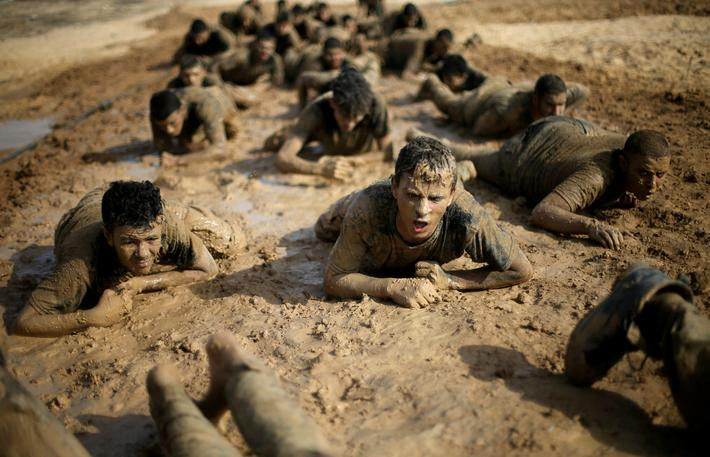 Young Palestinians crawl during a military-style exercise at a Hamas summer camp in Rafah in the sou