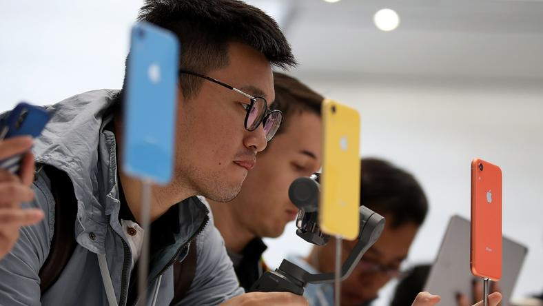 Visitors inspect the new iPhone XR during an Apple special event at the Steve Jobs Theatre on September 12, 2018 in Cupertino, California. Apple released three new versions of the iPhone and an update Apple Watch.