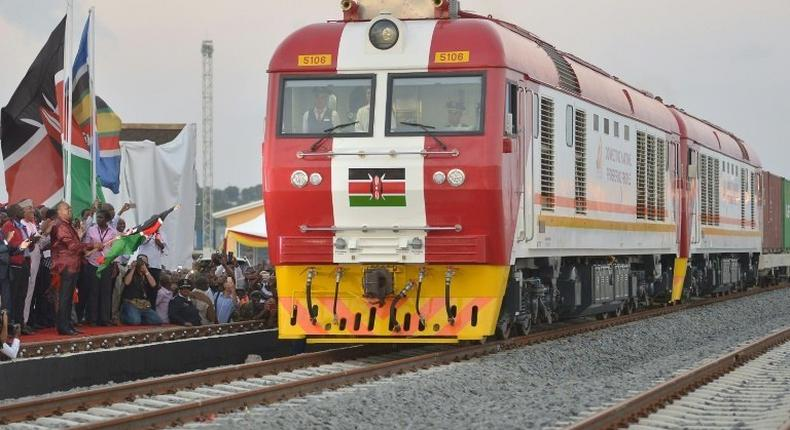 Kenyan President Uhuru Kenyatta flags off a cargo train at the port city of Mombasa on May 30, 2017, as it leaves the container terminal on its inaugural journey to Nairobi