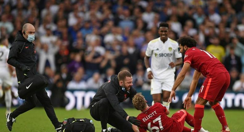 A trainer runs on the pitch to help Liverpool's Harvey Elliott (C) Creator: Oli SCARFF