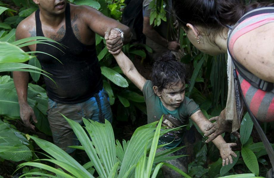 Cuban migrants help a child as they walk down crossing the border from Colombia through the jungle i