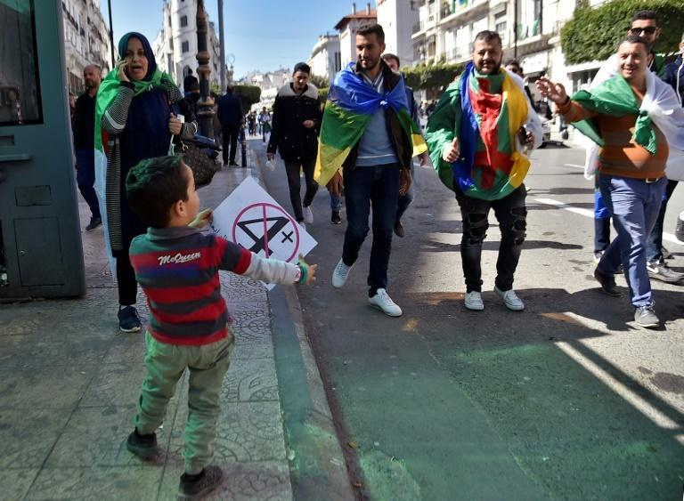 A child holds a protest sign as Algerians prepare for the first Friday rallies since the president's surprise announcement this week that he would not seek re-election but was cancelling April polls