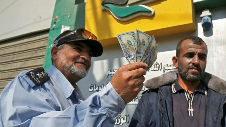 A Palestinian man shows his money after receiving his salary in Rafah in the southern Gaza Strip November 9, 2018