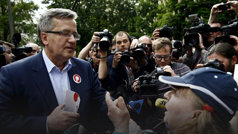 Poland's President Bronislaw Komorowski talks with a woman during his election campaign in Warsaw