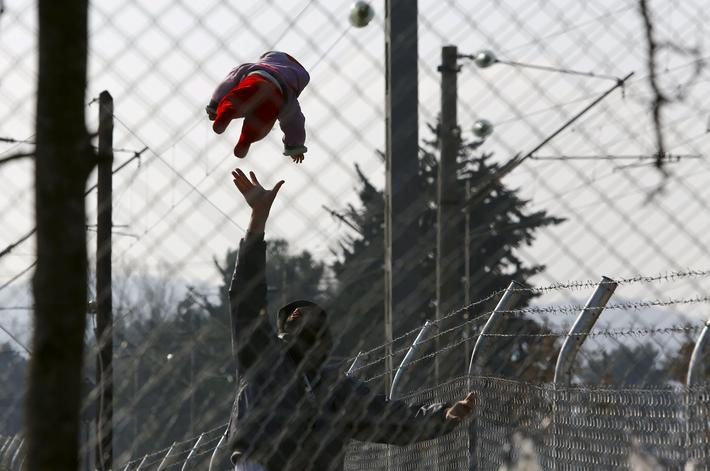 A migrant plays with his baby as they wait to enter Macedonia from Greece near Gevgelija, Macedonia
