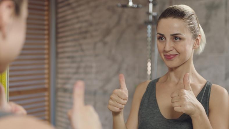 Kobieta dumna z siebie przed lustrem