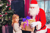 nova godina praznici dete paketići jelka paketić poklon deda mraz stock-photo-smiling-little-girl-with-santa-claus-and-gifts-over-christmas-tree-lights-background-328425683