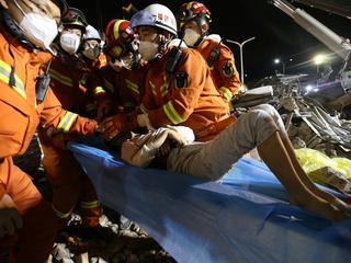 Rescue workers wearing face masks move a boy from the rubble of a collapsed hotel which has been used for medical observation following an outbreak of the novel coronavirus, in the southeast Chinese port city of Quanzhou, Fujian