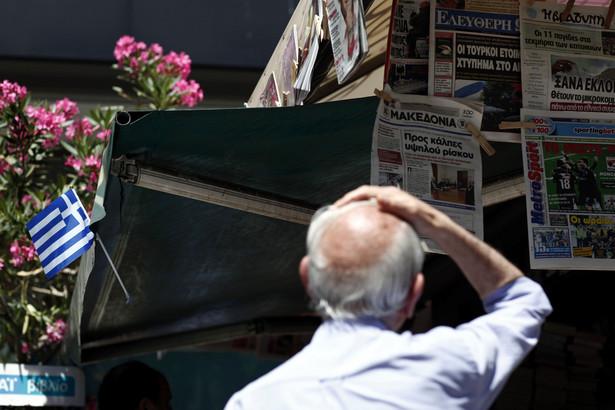 Mężczyzna patrzy na nagłówki gazet w Atenach
