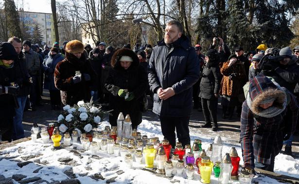 Adrian Zandberg przy pomniku ofiar wojen i represji w Hajnówce.