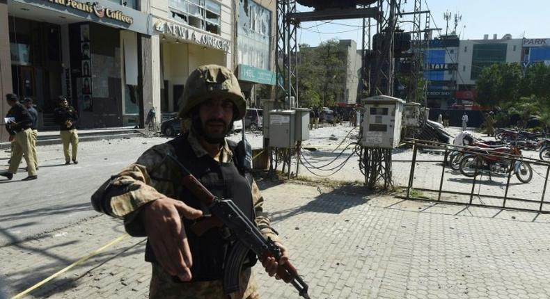 An Pakistani soldier cordons off the site of a bomb attack in Lahore, on February 23, 2017