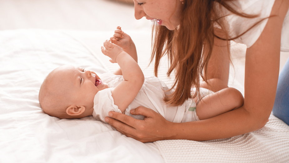 Niemowlę uśmiecha się w reakcji na czuły dotyk rodziców
