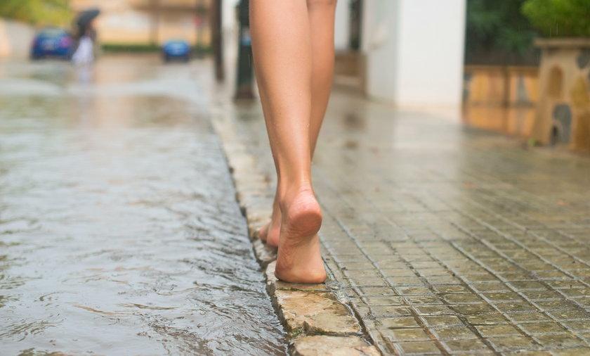 kobieta chodzi boso po ulicy
