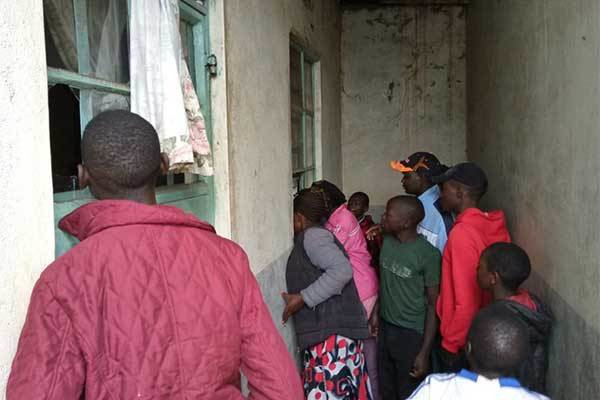 Neighbours peep into the house where a man slashed his wife to death before hanging himself to death in Trans Nzoia