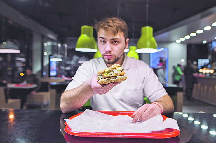 hrana, varenje, jelo stock-photo-a-handsome-man-holds-a-burger-in-his-hands-and-sends-him-to-the-camera-fast-tasty-food-focus-on-775295857