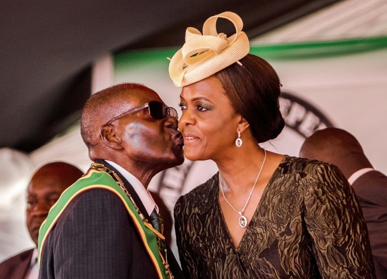 Former Zimbabwean ruler Robert Mugabe gives a cheek kiss to his wife Grace Mugabe.