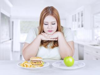 Confused woman choose apple or hamburger