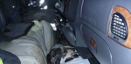 Właził do auta przez podłogę i utknął!
