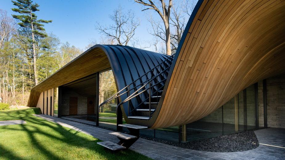 Dom w kształcie fali. Na dachu zielony taras z widokiem na park