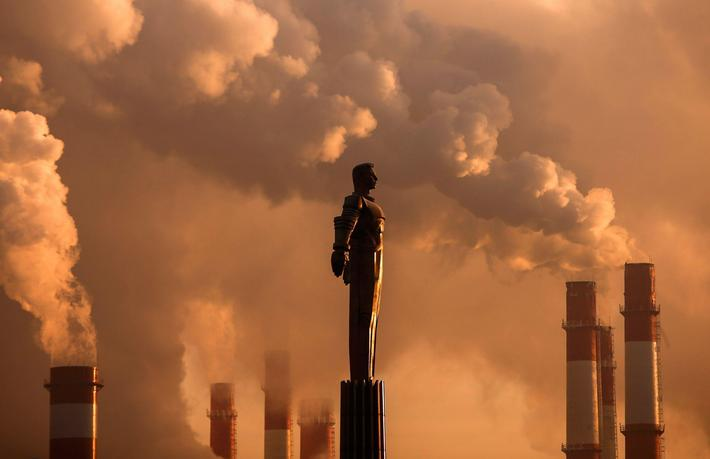 Steam rises from chimneys of a heating power plant near a monument of Soviet cosmonaut Yuri Gagarin