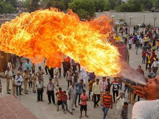 A Hindu devotee performs a stunt with fire during the Jal Yatra procession ahead of the annual Rath Yatra, or chariot procession, which will be held on June 25, in Ahmedabad