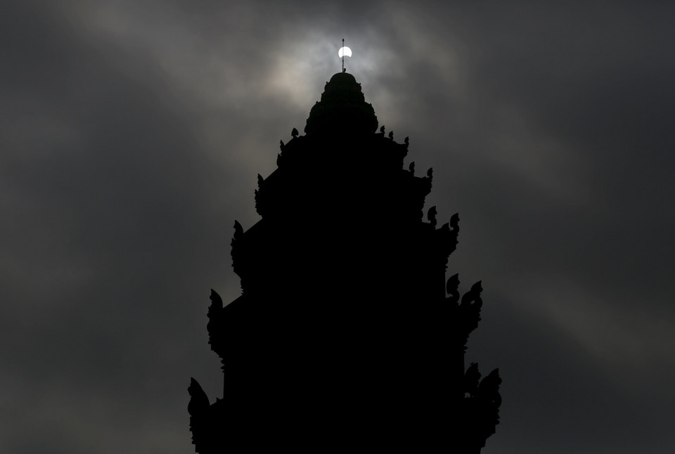 A partial solar eclipse is seen over the Independence Monument in Phnom Penh, Cambodia