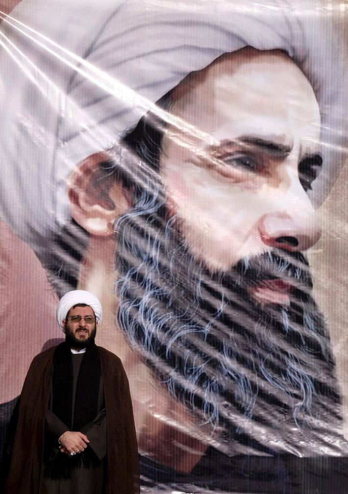 Iranian cleric stands in front of a poster of prominent Shi'ite cleric Sheikh Nimr al-Nimr during a