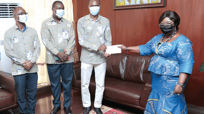 Mrs Akosua Frema Osei Opare receiving a cheque from Dr John Amaglo President, Ghana Institute of Surveyors