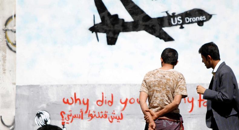 Men look at wall graffiti depicting a U.S. drone along a street in Sanaa, Yemen, November 9, 2013.