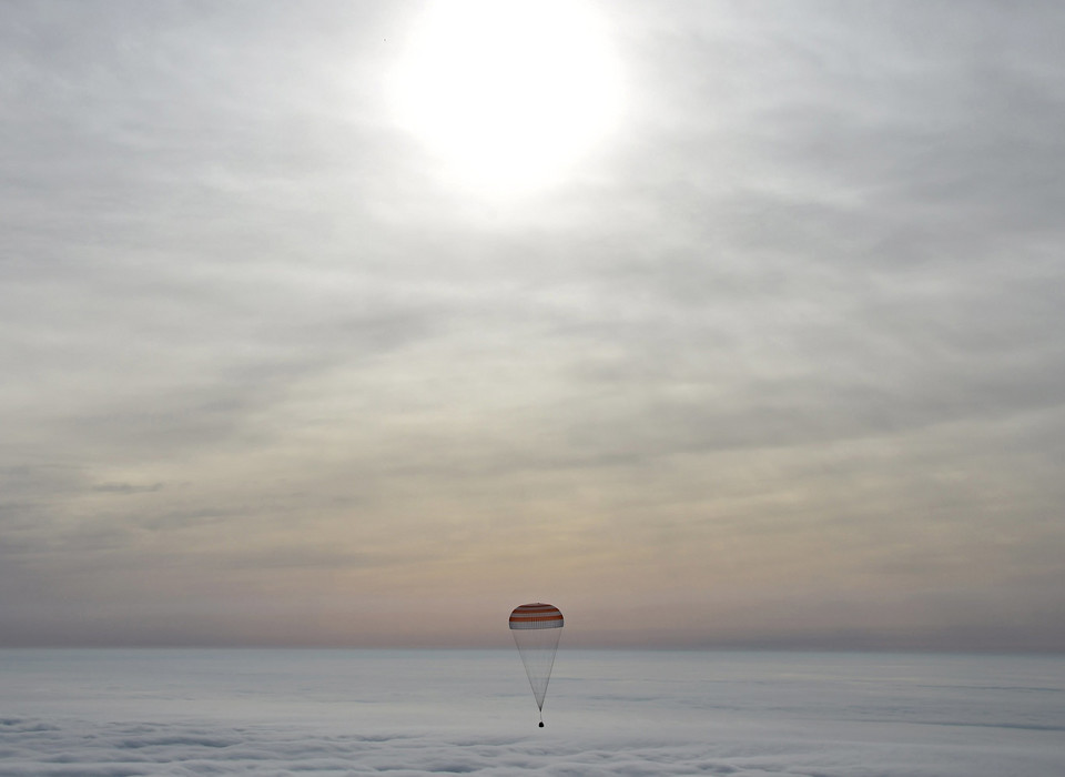 A Soyuz capsule carrying International Space Station (ISS) crew members U.S. astronaut Scott Kelly, Russian cosmonauts Sergei Volkov and Mikhail Korniyenko descends beneath a parachute near the town of Dzhezkazgan